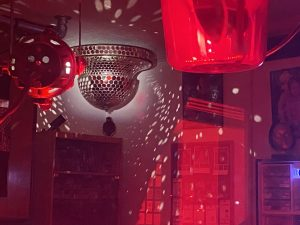 A photo of our mirror ball reflecting the red lights inside our showroom